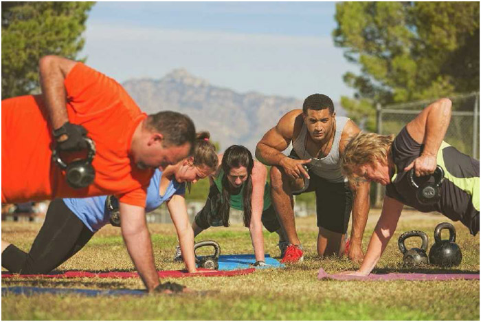 A trainer instructs his class in kettleball exercises during an outdoor boot camp.
