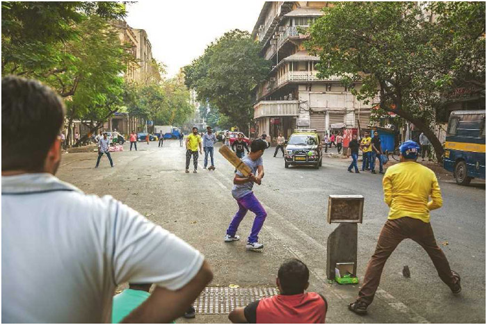A group of men play cricket in the streets of downtown Mumbai, India, January 2016. Although the sport originated in England, cricket has spread to many countries around the world and is the most popular sport in India today.