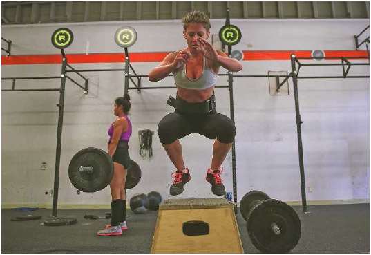 Women train at Ross Valley CrossFit in San Anselmo, California, March 2014. CrossFit is a program that combines weightlifting, sprinting, powerlifting, rowing, gymnastics, and other such activities for a full-body workout.
