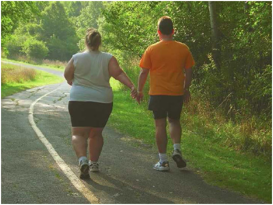 An overweight couple takes a walk as part of their exercise routine. Physical inactivity is one factor that places a person at risk of obesity-related diseases and conditions.