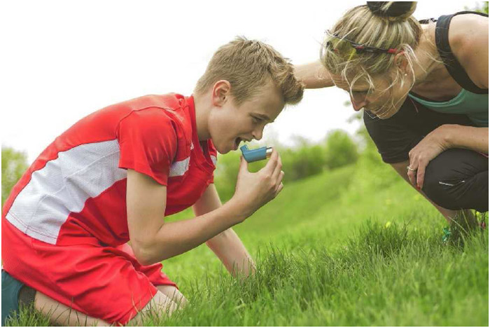 A young soccer player takes a break to use his inhaler. Exercise-induced asthma is caused by cool, dry air entering the lungs, which typically occurs when breathing through the mouth instead of the nose.