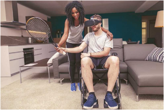 A man wearing virtual reality (VR) goggles gets help from a trainer while exergaming. Exergaming aims to make exercise an enjoyable experience by combining entertainment with physical activity.