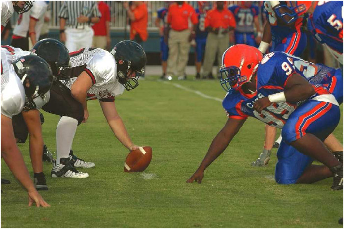 Two football teams take their positions as they prepare for the center to snap the ball. American football is one of the most popular sports in the United States, with the annual Super Bowl being the most-watched sporting event in the country.