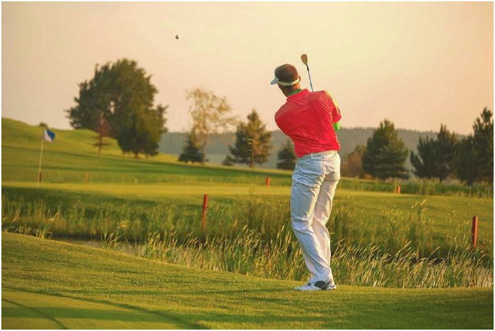A left-handed golfer uses one of his irons to loft the ball over water and toward the green.
