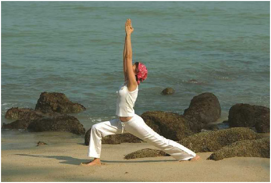 A woman holds the Warrior I asana (a yoga pose) on the beach. Hatha yoga is the most widely practiced form of yoga in the world.