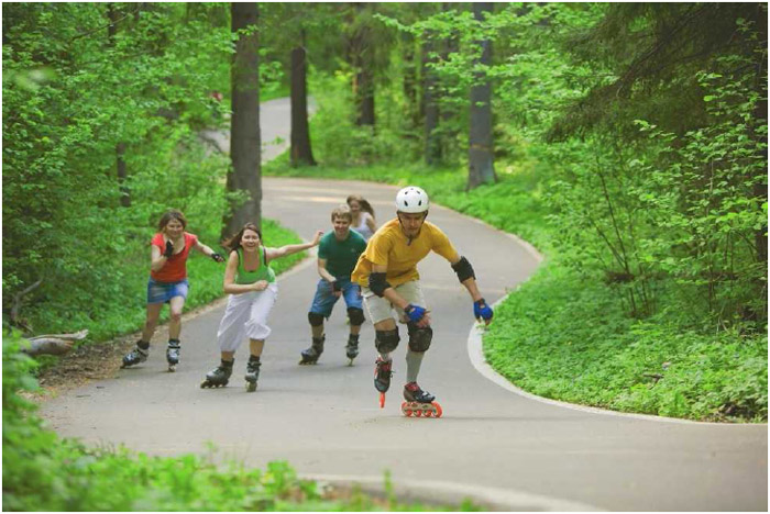A group of young adults skate along a paved road. While there are competitive variations of inline skating, most participants enjoy skating purely as a form of recreation.