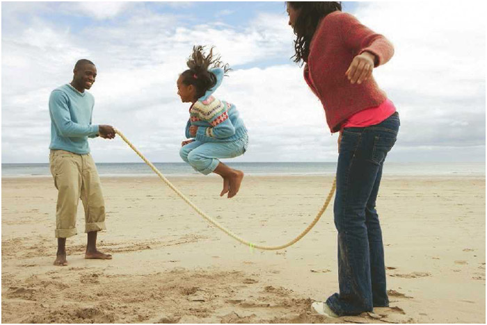 A family jumping rope on the beach.