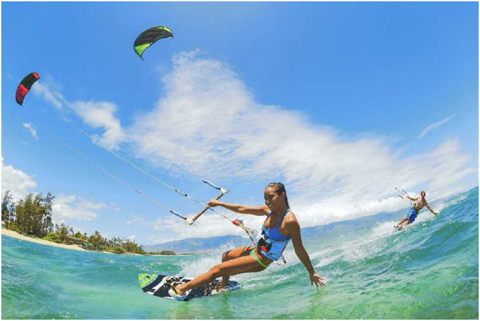 A young woman and man kite surf in the ocean. Most ocean sports are enjoyed recreationally, as very little advance conditioning or training are needed to participate.