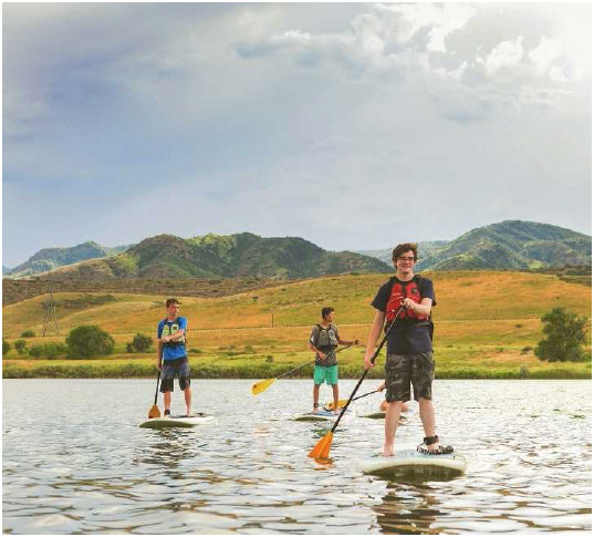 Teenagers paddleboard on a pond in Denver, Colorado. Paddleboarding is a good way to exercise core muscles, as it requires balance and the ability to propel oneself through the water.