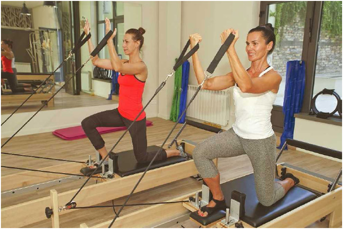Two women demonstrate how to use a Pilates Universal Reformer. Pilates consists of nonimpact exercises that help develop strength, flexibility, and balance.