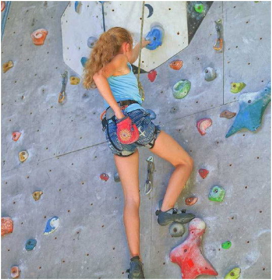 A young girl climbs an artificial rock wall. Rock climbing is a recreational and competitive sport that requires strength, endurance, flexibility, and balance.