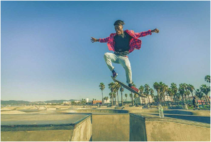 A skateboarder jumps over a gap at a skate park. Skateboarding is a cardiovascular exercise that requires balance and coordination.