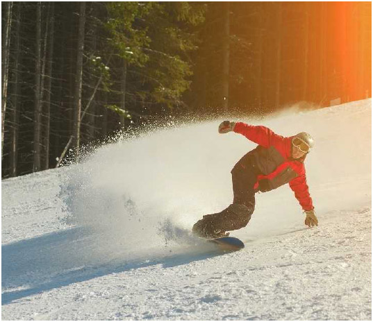 A snowboarder sprays snow into the air as he makes a turn on the hill. Originating in the 1960s from a combination of skateboarding, skiing, and surfing techniques, snowboarding is a relative newcomer to the field of winter sports.