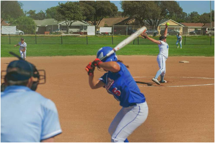 A softball pitcher winds up to deliver her pitch to the batter. Participating regularly in softball games and associated practice strengthens muscles, boosts cardiovascular health, and improves balance and coordination.