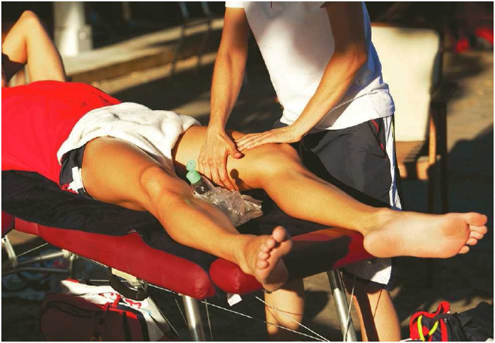 An athlete receives a leg massage while lying on a gurney. Sports massage therapy is often used to prepare an athlete's muscles for rigorous use or to reduce the muscles' recovery time during training or after a sporting event.