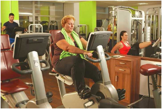 A woman exercises on a stationary bicycle at her fitness center. Stationary bicycles provide a low-impact aerobic exercise that strengthens back, leg, and thigh muscles without putting too much strain on the body.