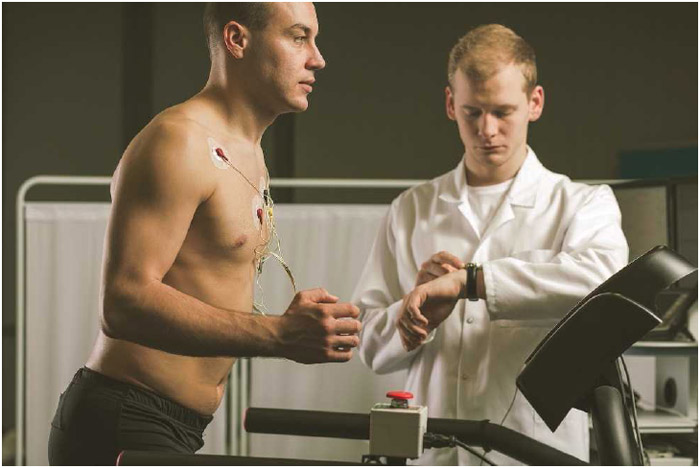 A doctor monitors a patient who is performing a stress test. Stress tests examine a person's cardiovascular capacity by measuring heart rate during increasingly strenuous exercise, typically on a treadmill.