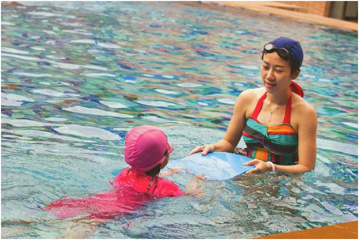 A mother and daughter use a kickboard to help the young girl learn how to swim.