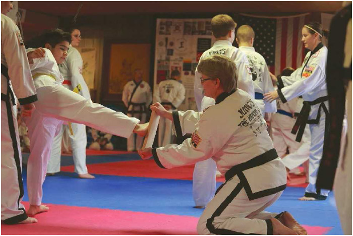 A young tae kwon do student attempts to kick through a wooden board at a dojang (training hall) in Cedar Rapids, Iowa, December 2016.