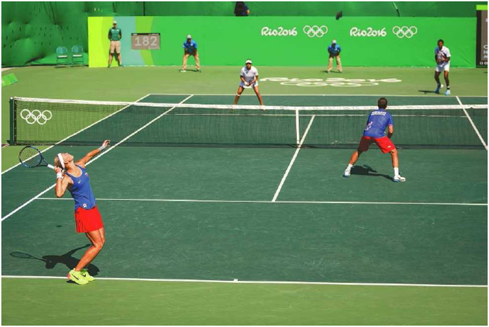 Lucie Hradeckdof the Czech Republic serves the ball to Sania Mirza and Rohan Bopanna of India during the bronze-medal mixed doubles match of the 2016 Olympics in Rio de Janeiro, Brazil, August 2016.