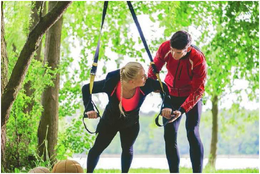 A personal trainer helps a woman exercise using TRX suspension trainers. TRX trainers leverage gravity and the user's body to strengthen muscles. (