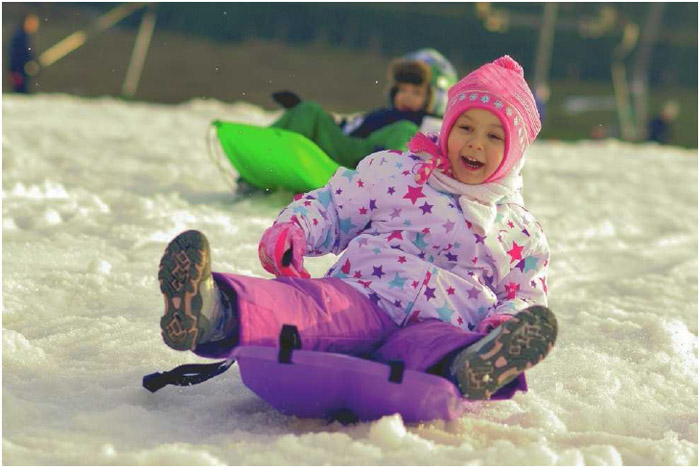 A little girl plays in the snow on her sled. Many winter sports can be enjoyed recreationally or competitively.