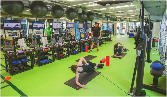 Google employees exercise at the workplace fitness center in Munich, Germany, April 2016.