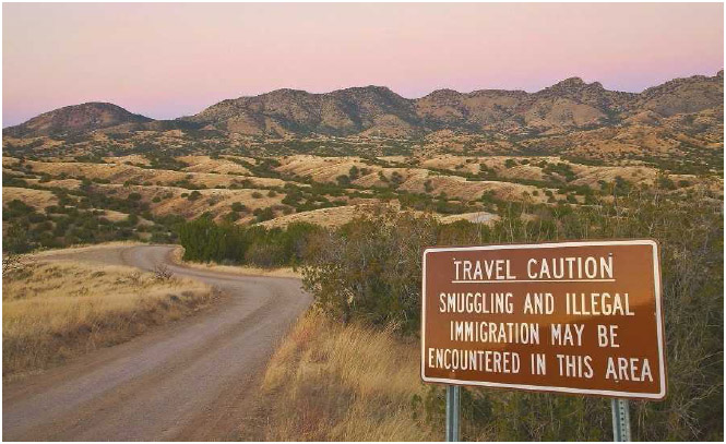One of the many dirt roads in the Santa Rita Mountains, near Sonoita, Arizona, marked with smuggling and illegal immigration warning signs.