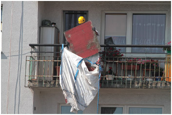 Asbestos boards being removed from the balconies of postcommunist block apartments.