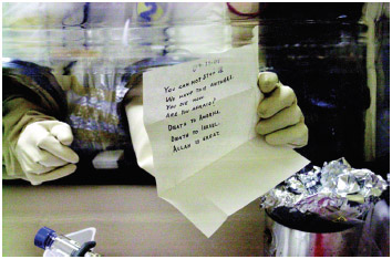 A laboratory technician holding an anthrax laced letter, after safely opening it, addressed to Senator Leahy at Fort Detrick bio-medical research laboratory in the Amerithrax investigation.