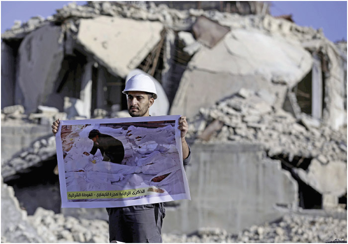 A member of the Syrian civil defense organization, White Helmets holds a photo of a person who lost his life in a chemical attack that occurred in the Eastern Ghouta region of Damascus, Syria, on August 22, 2017,