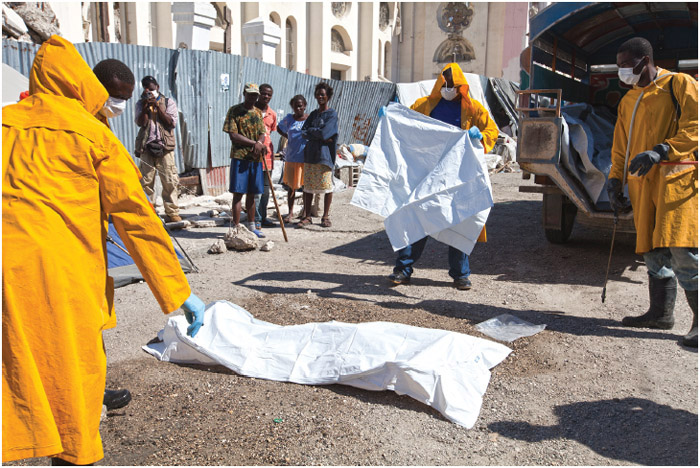 Minister of Health workers prepare Charite Charle's body, a cholera victim, found dead next to the National Cathedral in Portau-Prince, Haiti, where she lived on the streets with her two children.
