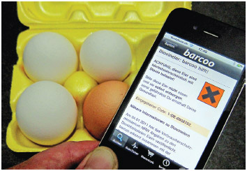 An iPhone with the 'barcoo' app is held over a carton with eggs in Cologne, Germany, 8 January 2011.