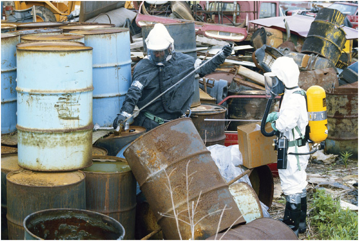 Encased in full-body protective suits, Environmental Protection Agency workers test barrels of waste at a dumping site near Houston, Texas.