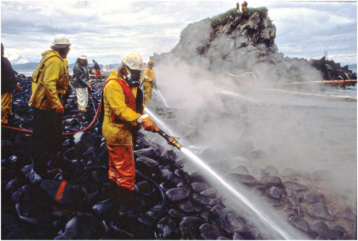 Workers blast rocks and wash down the shoreline soaked in crude oil using Corexit oil dispersant during a test during clean up operations on Quayle Beach, Smith lsland from the Exxon Valdez oil spill August 8, 1989 in Prince William Sound, Alaska.