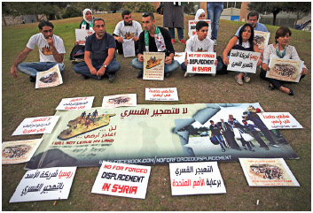 In this picture taken on Friday, Oct. 7, 2016, Syrian citizens attend a sit-in against the forced displacement in Syria, in front the United Nations headquarters, in downtown Beirut, Lebanon.