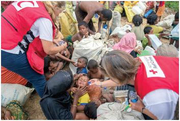 Red Cross volunteers give oral rehydration solution to exhausted Rohingya Muslim children, who spent four days in the open after crossing over from Myanmar into Bangladesh,