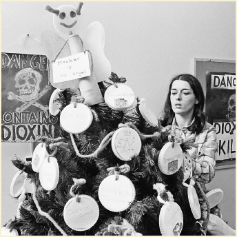 Lois Gibbs, president of the Love Canal Homeowners Association, makes adjustments to a Christmas tree trimmed with decorations naming some of the chemicals found in the Love Canal, Dec. 21, 1978.