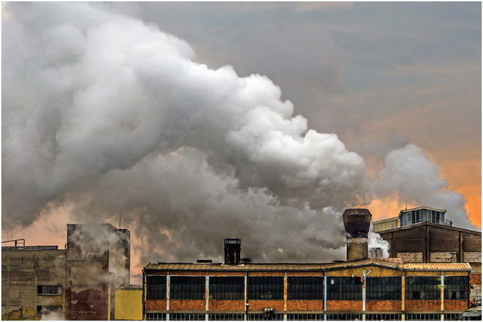 Old factory polluting the atmosphere with smoke and smog.