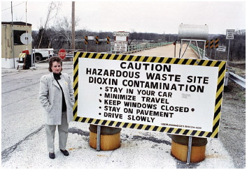 Marilyn Lestner, former mayor of Times Beach, Mo., stands next to a caution sign at the entrance to the town of Times Beach, April 3, 1991. Nearly a decade after dioxin was discovered in Times Beach, the abandoned town was be bulldozed and buried.