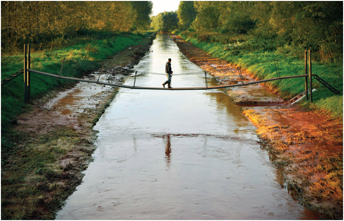 A man walks across a foot-bridge over the River Marcal containing the toxic red sludge that spilled from a giant industrial container near Mersevat, Hungary on Thursday, October 7, 2010.