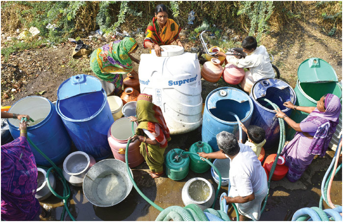Villagers of Masurdi, Ausa, filling water after having to queue for 3 hours before water tanker comes to their village point on April 11, 2016 in Latur, India.