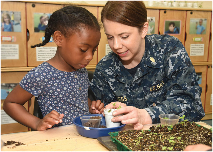 """A registered dietician teaches a child how to plant basil as a part of the hospital/s efforts to promote """"Put Your Best Fork Forward,"""" a part of National Nutrition Month,"""