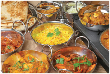 Traditional Indian foods, including curry, naan bread, and rice.