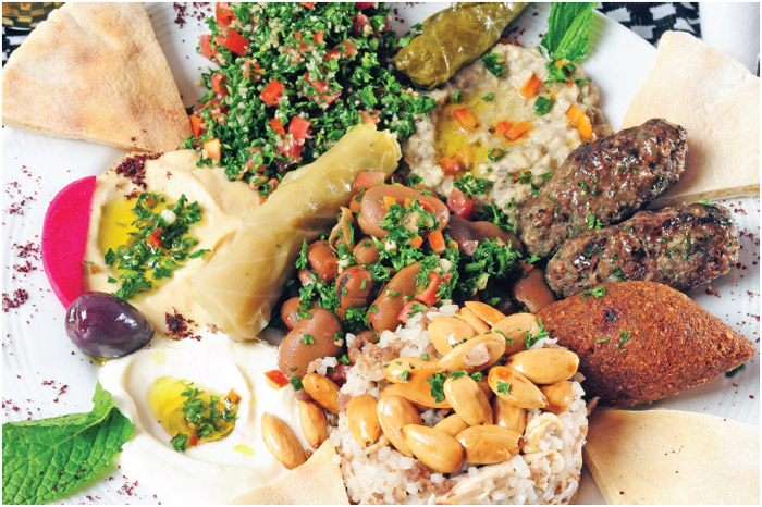 Lebanese meal including hummus, pita bread, tabouli, grape leaves, rice, and lamb.