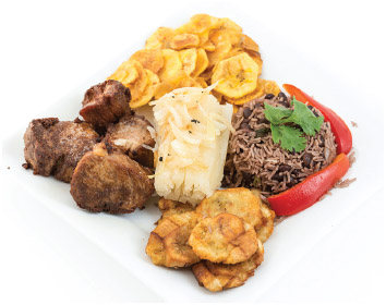 Plate of traditional Cuban cuisine: fried pork, congri rice, green banana chips, boiled cassava or yukka.