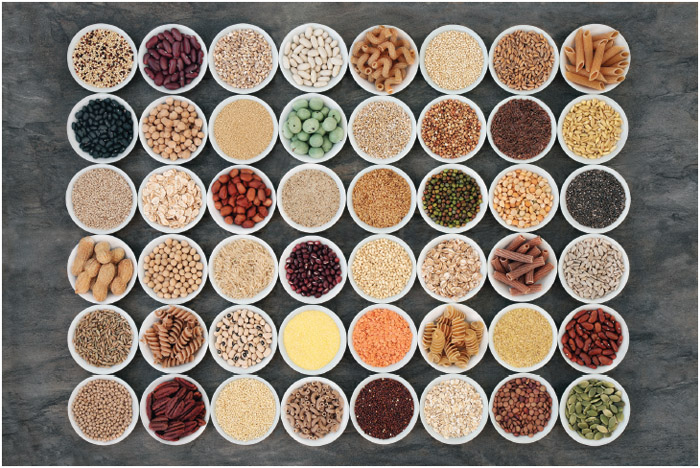 Macrobiotic health food with a selection of legumes, seeds, nuts, grains, vegetables, cereals, and whole wheat pasta with super foods high in protein, omega-3, anthocyanins, antioxidants, and vitamins.