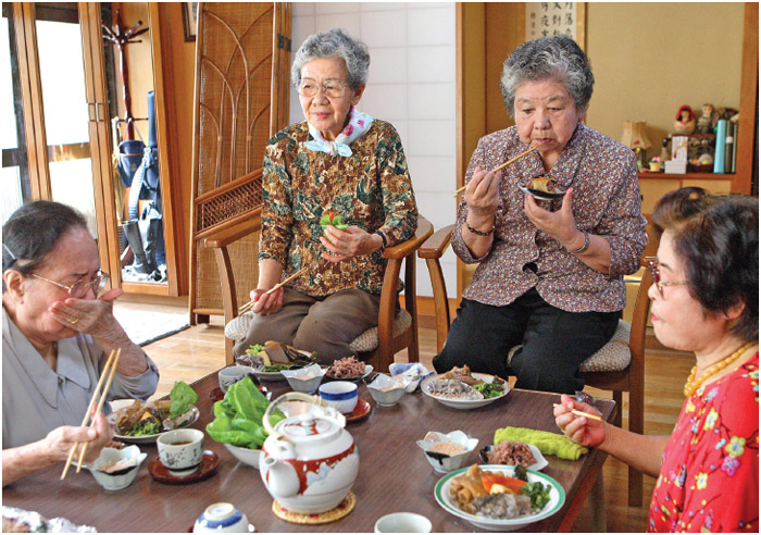 Women have Okinawa's traditional dishes for lunch in Okinawa, Japan.
