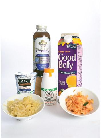 A display of various types of probiotics, including sauerkraut, kimchi, cultured goat milk, yogurt, kombucha, and probiotic juice drink.