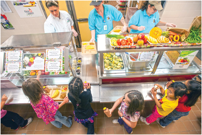 Elementary school children in line at cafeteria being served healthy lunches.